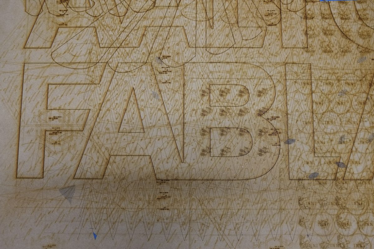 laser cutter spoilboard with the letters FABL visible