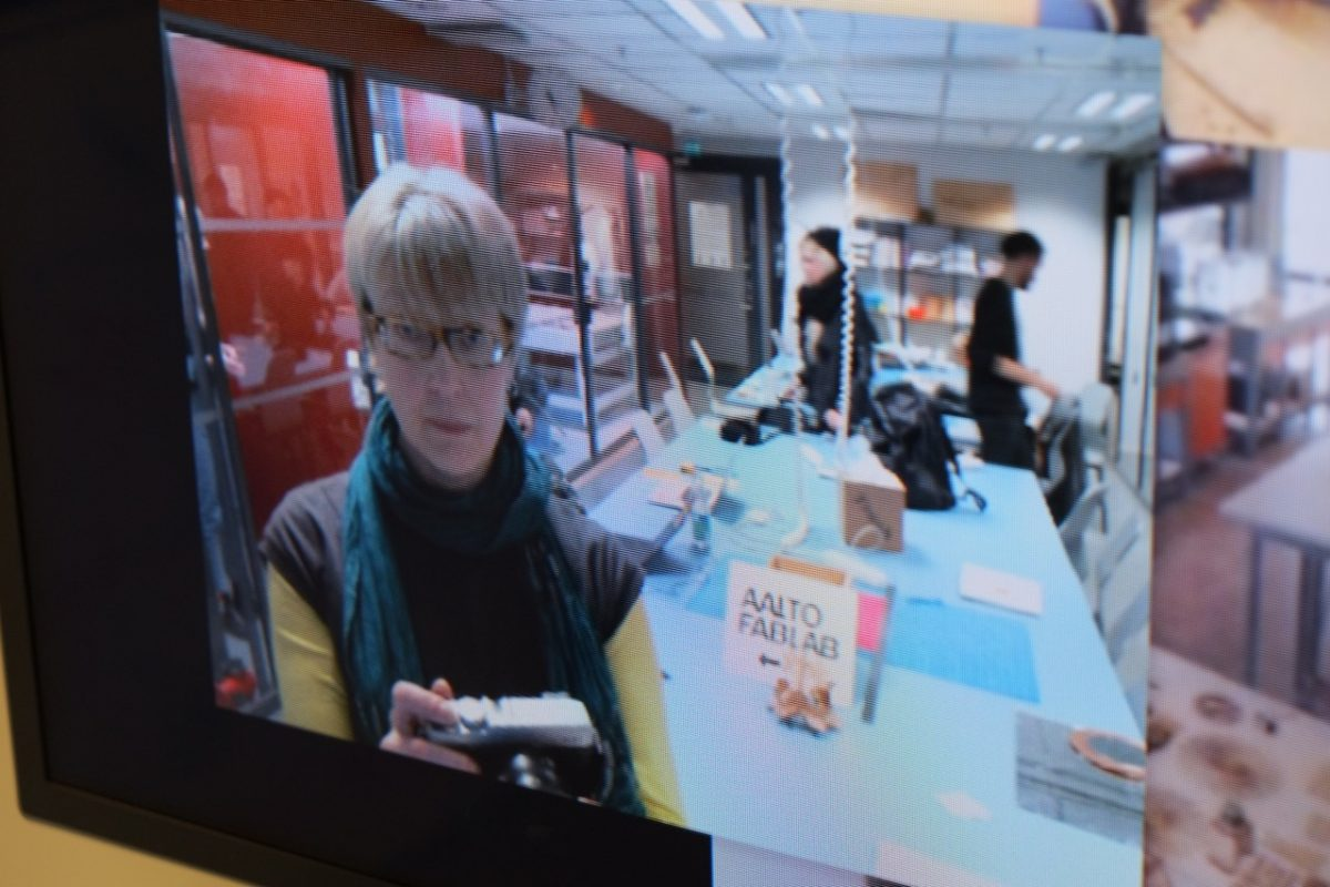 photo of a large screen showing the webcam in a fab lab, with a person taking a photo in the foreground and a large table in the background