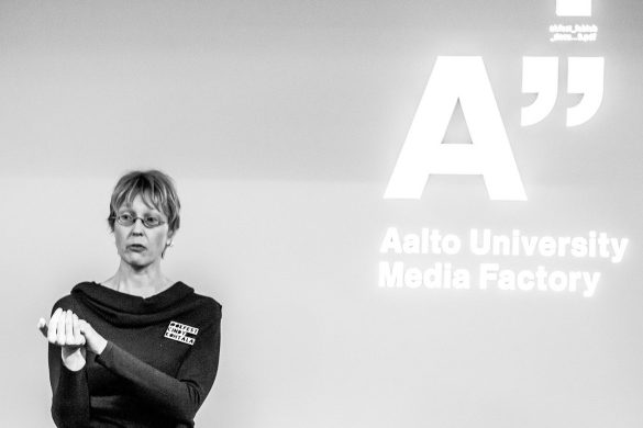 photograph of a speaker at an event with the logo of the venue, Aalto University Media Factory, in the background