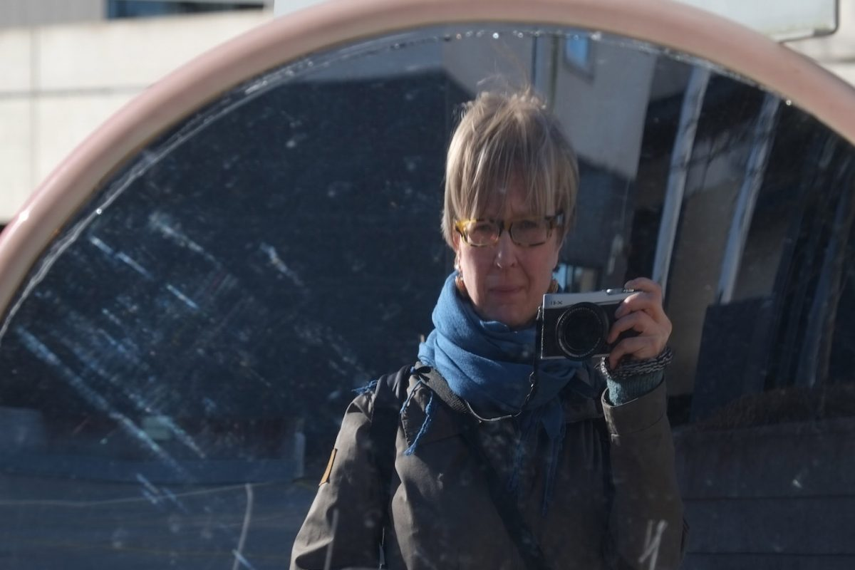 photograph of a person taking her own photo in a traffic mirror