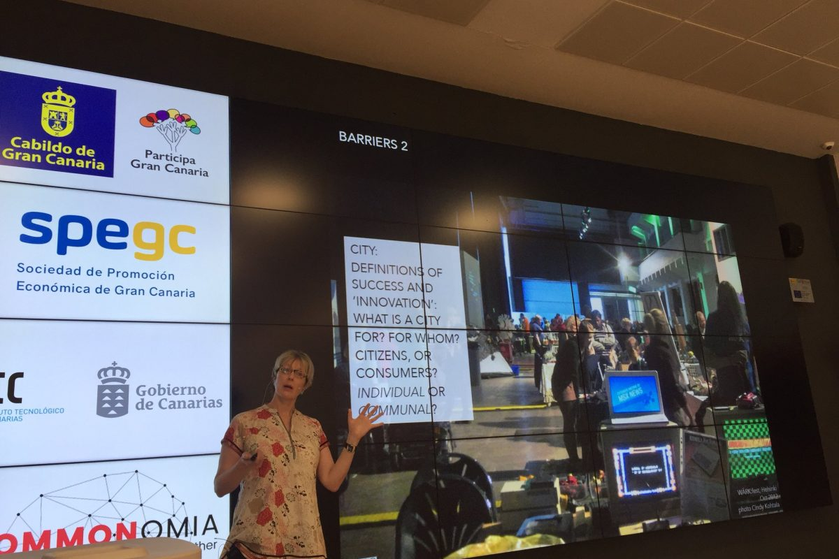 """photograph of a presenter with her hand up in front of a very large screen that has her slide in most of the photograph on the right and the logos and information about the information and organizers in sections along the left hand side of the stage and what is viewable in the photograph. the presenter's slide has a photograph of a maker event and a text box reading, """"CITY: DEFINITIONS OF SUCCESS AND 'INNOVATION': WHAT IS A CITY FOR? FOR WHOM? CITIZENS OR CONSUMERS? INDIVIDUAL OR COMMUNAL?"""