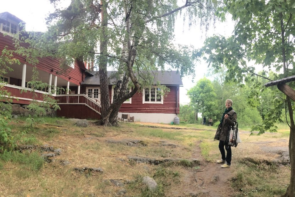 panorama photograph of a large log community hall in traditional Nordic ochre red colour with white trim surrounded by trees and me standing in the mid-ground on the right of the photo looking at the camera and smiling