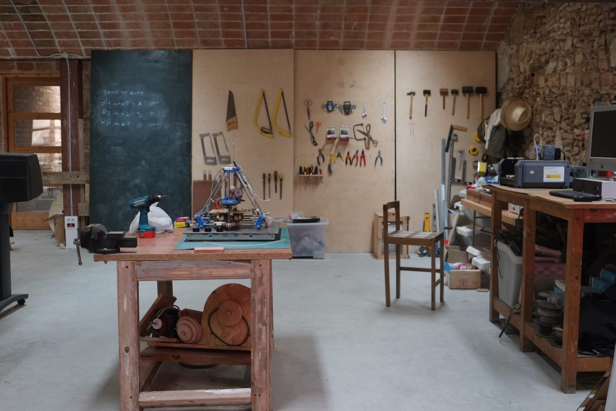 photograph of the interior of the fab lab space, which has brick walls and ceiling. along the back wall is a blackboard and wood panels for hanging handtools. a workbench in the foreground has a reprap 3D printer on it, a vice grip and a hand drill. along the other wall is a workbench with a small milling machine, computer.
