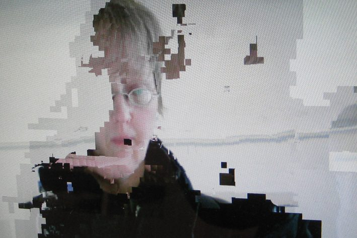 photograph of a face on a screen that is pixelated