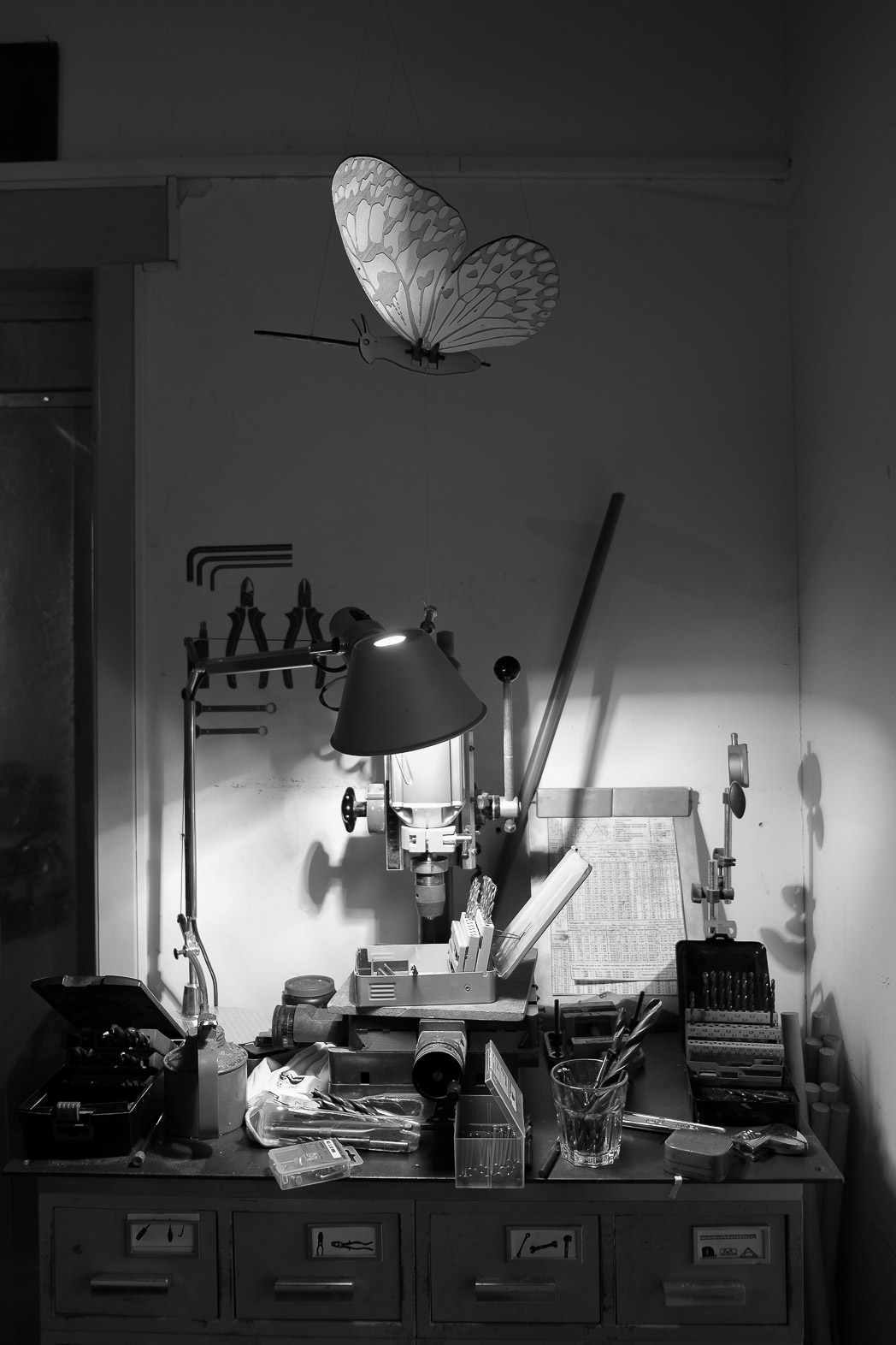 photograph of a detail inside FabLab Amsterdam of objects on top of a shelf of drawers for tools: there are drill bits, a drill press, a desk lamp lighting the scene dramatically and a laser cut and etched butterfly flying over the scene