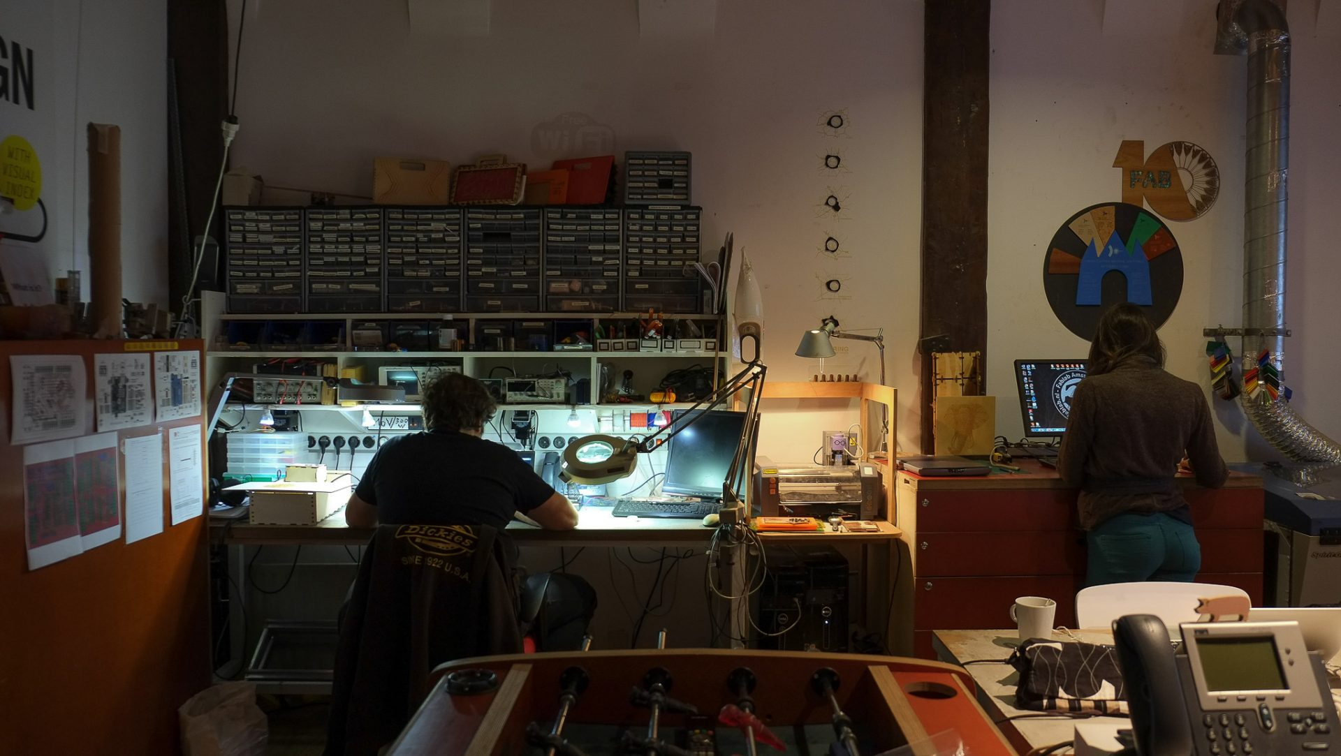 photograph of FabLab Amsterdam, interior. one person is seen from the back sitting at an electronics station lit by a magnifier desk lamp. there are racks of electronics components above the desk. on the right another person is standing working at a computer. everywhere there are various tools and fab lab miscellaneous objects.