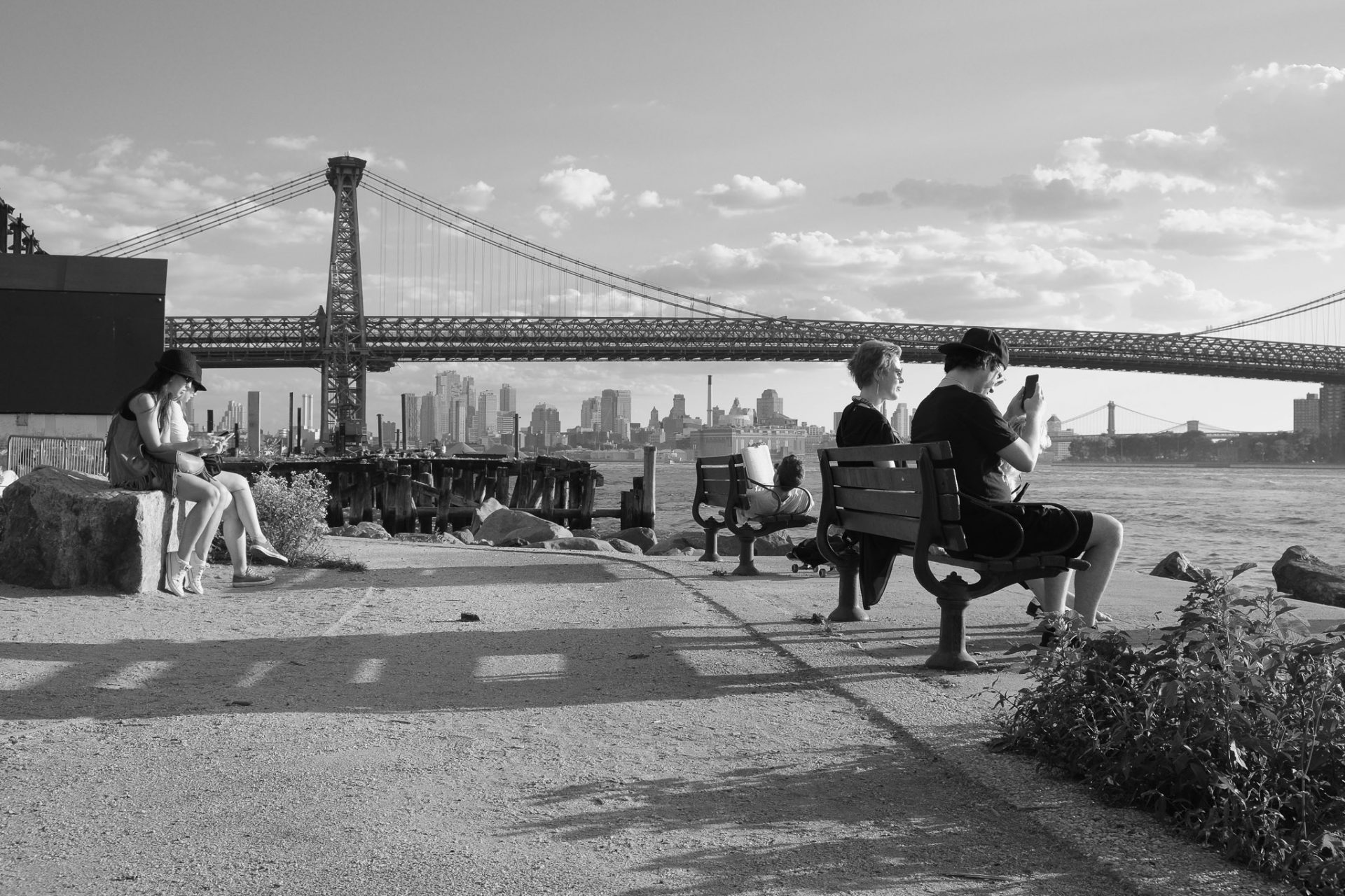 black and white photograph of Williamsburg, Brooklyn, near the river. the Williamsburg Bridge is visible in the background as a compositional element. there are two benches looking towards the river and towards Manhattan. on one bench a woman is sitting looking forward and a young man with a baseball cap backwards is looking at his phone. on the other bench a man is lying down reading a newspaper. he has a skateboard on the ground beside him. on the left side two people, maybe tourists, are sitting on a rock looking at their phones.