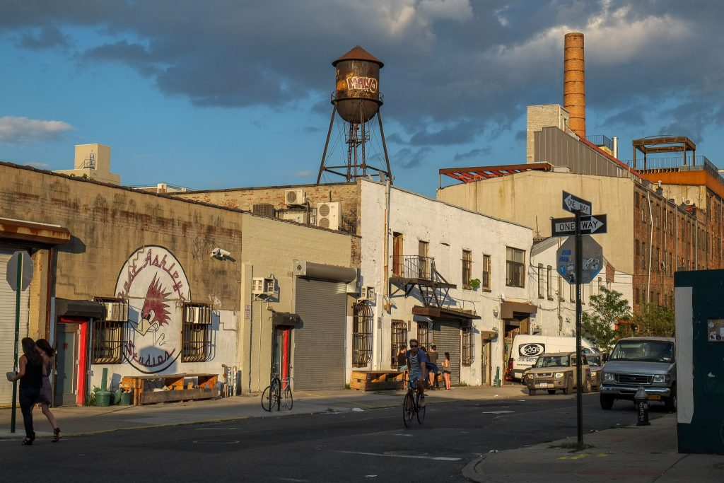 photograph of a street scene in Greenpoint, New York. a water tank sits up on the roof of a building, with graffiti on it. the evening sun is lighting the scene. a bicyclist is riding down the street.