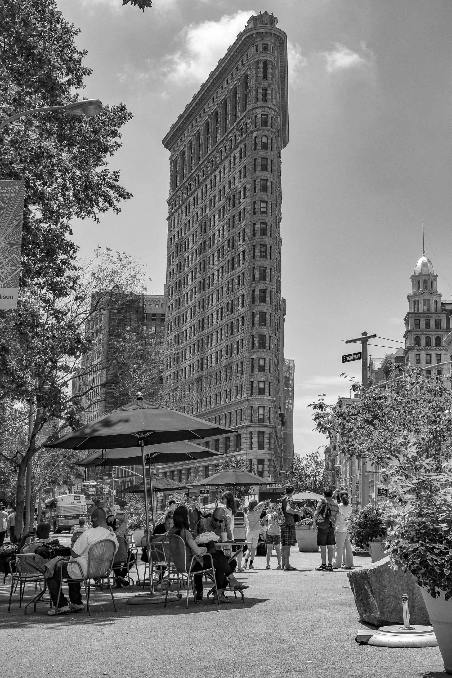 black and white photograph of the Flatiron building in Manhattan and the street scene in front of it, with people sitting at cafe tables