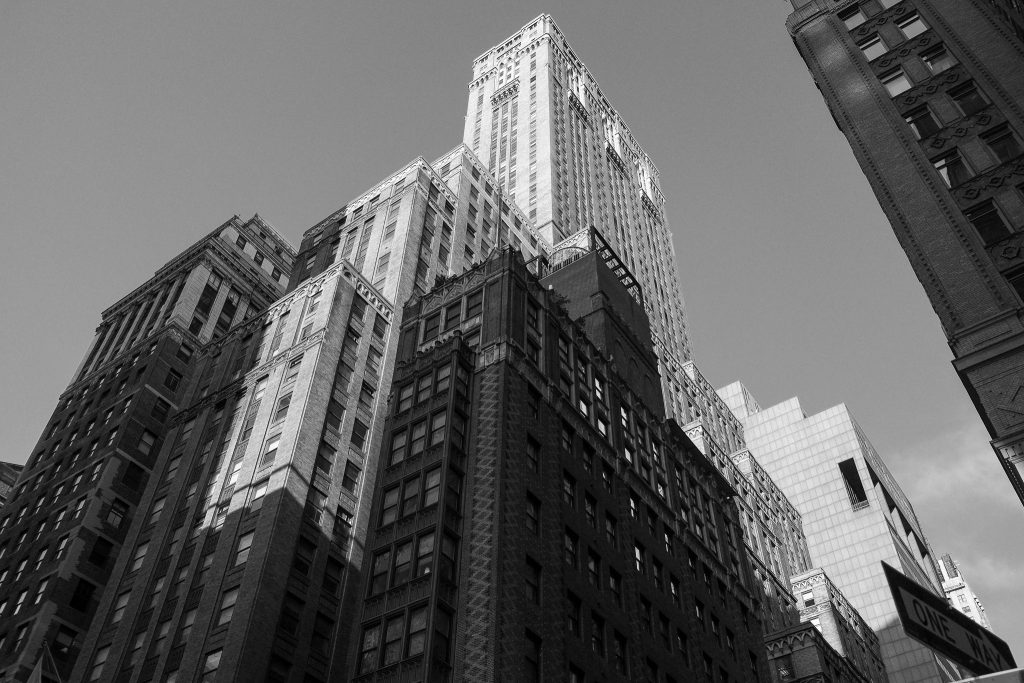 black and white photograph of Manhattan architecture from the street level looking up