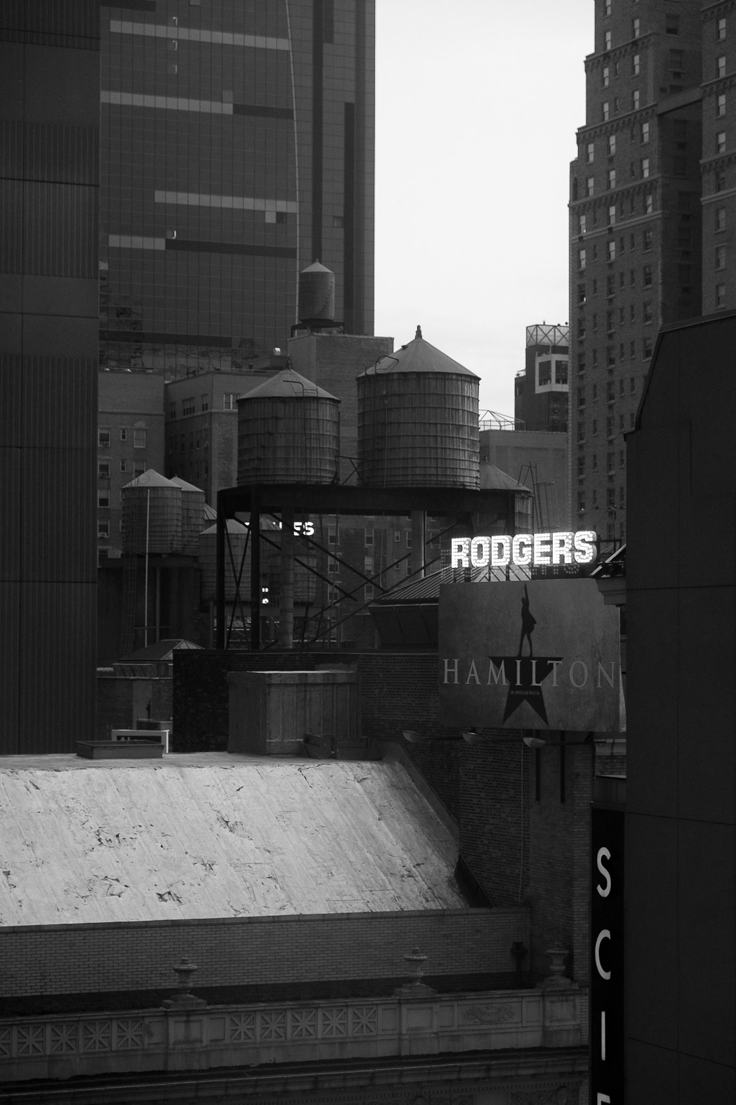 black and white photograph of a Manhattan scene. a neon sign of white lights reads, RODGERS. below it is an advertising hoarding for Hamilton. there are many water tanks on various levels and several skyscrapers.