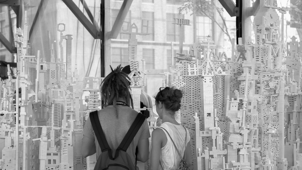 black and white photograph of Eliasson's collectivity project, which is a huge amount of white legos on many tables. people have built up the legos into many structures and tall teetering towers. two people are in the photograph, seen from the back, looking at the legos.