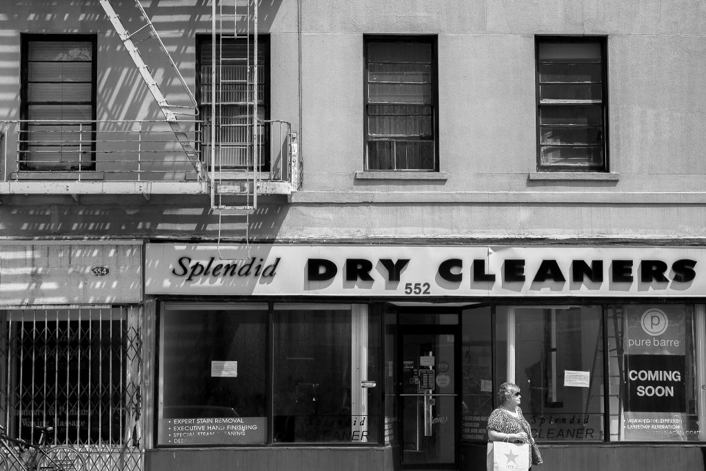 black and white photograph taken in Manhattan. a sign over a shop reads, Splendid Dry Cleaners in attractive typefaces where the sun is creating shadows. there is a row of windows above the shop and a fire escape on the left side, also creating dramatic shadows. a woman wearing sunglasses and carrying a shopping bag is on the street in front of the dry cleaners.
