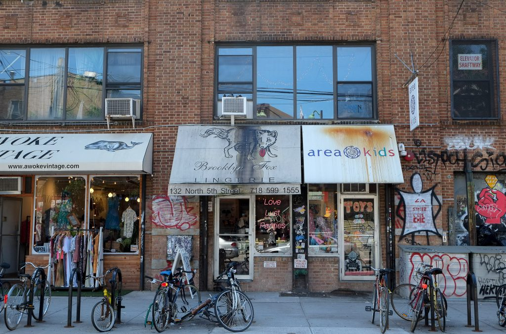 photograph of a street and shops in Williamsburg, New York. the building is brick and the shop have awnings with graphically expressive shop names. one shop has a display clothes rack outside. another shop has neon signs in the window. there is graffiti on the building and a lot of bicycles parked outside.