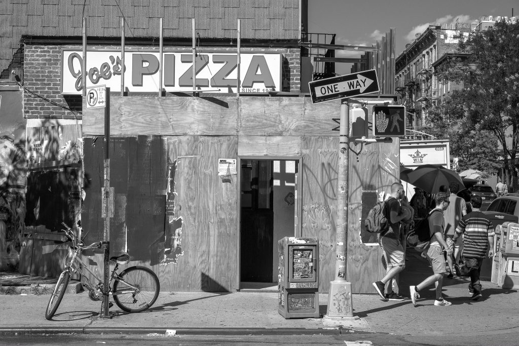 black and white photograph of a Brookelyn street corner. it is a collage of graphics and materials, with a construction site covered in plywood, a sign saying Joe's PIZZA, a newspaper box, a one-way sign, a bicycle locked to a parking sign, traffic lights, people walking round the corner.