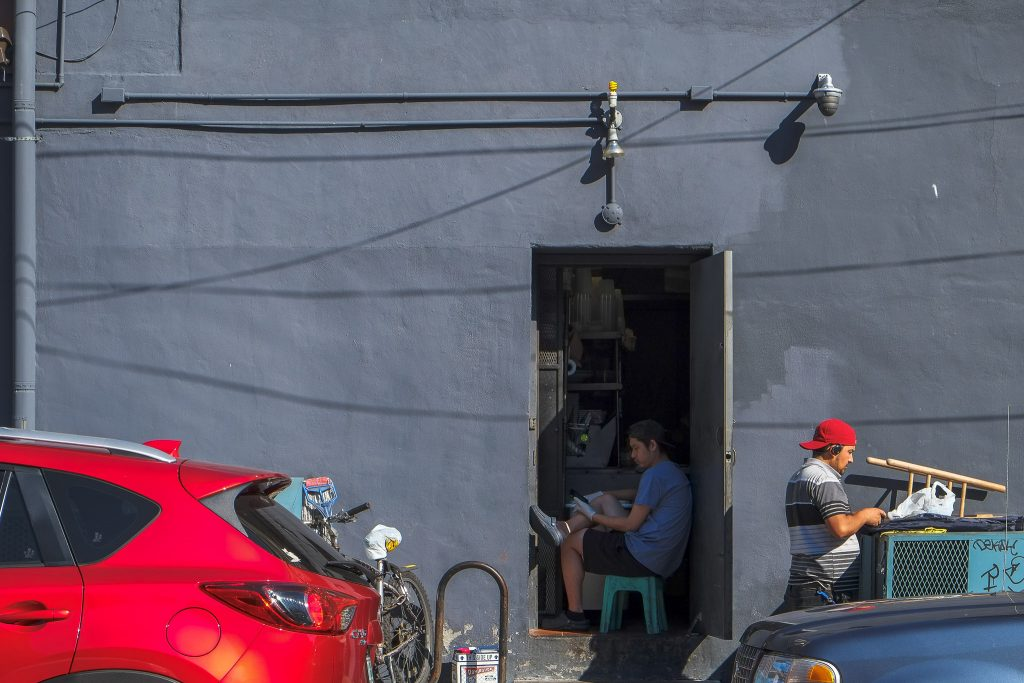 photograph of the back side of a building. a plain blue-grey plaster wall dominates the image. there is an open door in which a guy who looks like a worker in the place is sitting. he's wearing a t-shirt, shorts and a baseball cap backwards. he's wearing gloves. in front of the building is another guy wearing a cap and holding some stuff and some parked cars.