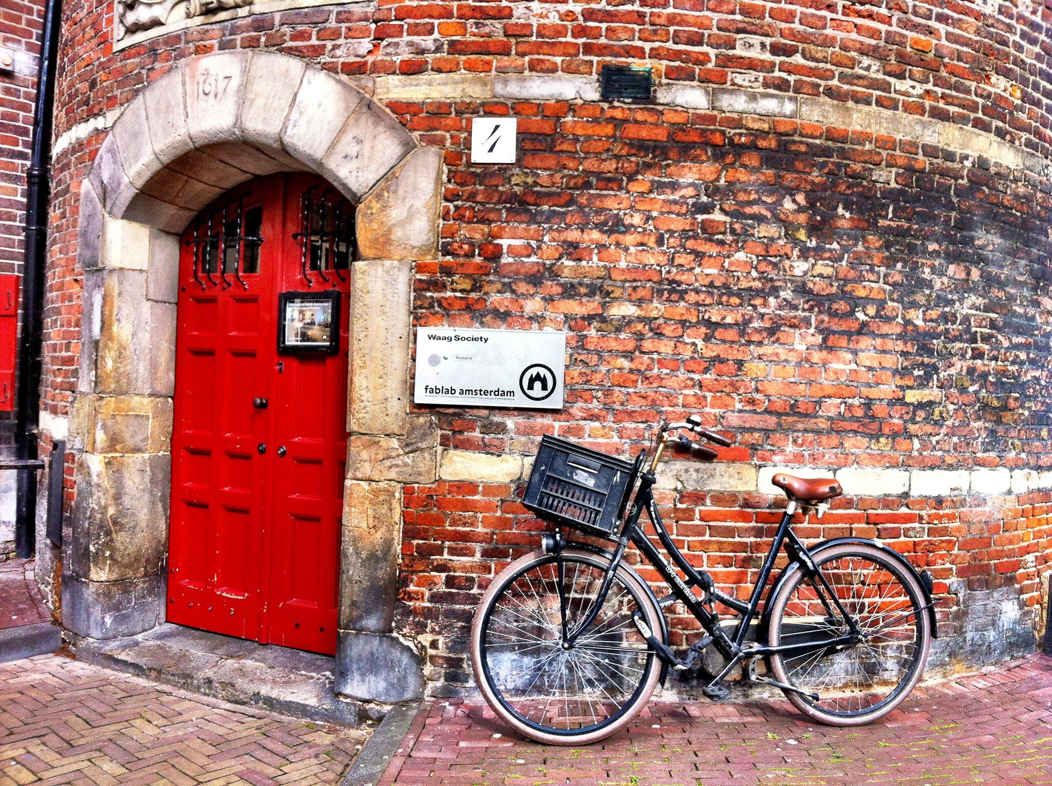 photograph of the Waag Society building, Nieuwmarkt, Amsterdam, showing the door to FabLab Amsterdam. the building is historic, brick, and the brick wall is curved and aged. the doorway is stone and the double door is red. there is a typical Amsterdam black bicycle parked near the door under a sign reading fablab amsterdam.