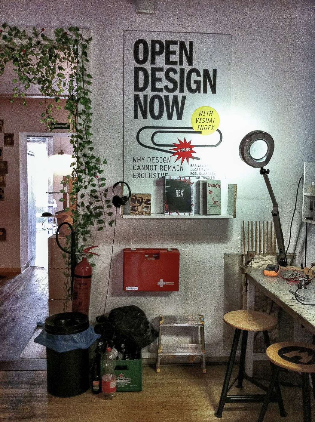 photograph inside FabLab Amsterdam. the electronics soldering desk is visible on the right and in the centre of the photo there is a display shelf showing some books. under the shelf is a first aid kid, a small step ladder, a beverages craft and a rubbish bin. on the left there is a doorway with a vine plant growing up the wall and over the doorway. the main focus in the photo is a large poster on the wall which is the cover of the book Open Design Now