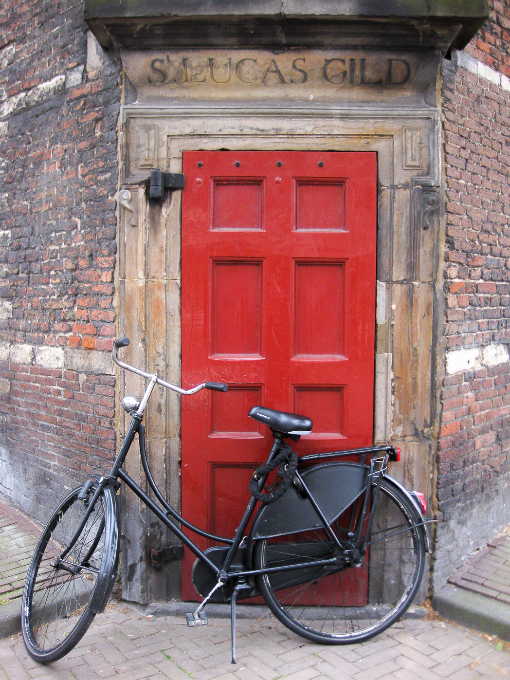 photograph taken outside the distinctive and historically important Waag Society building at Nieuwmarkt in Amsterdam. there is a red door, above which is a stone chiselled sign saying St Lucas Guild. in front of the door there is a typical Amsterdam black bicycle.