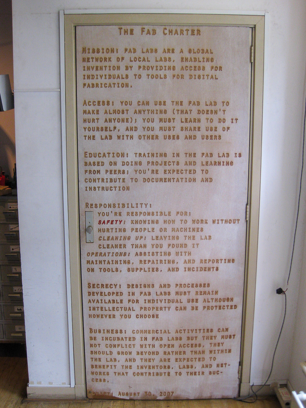 photograph of the Fab Charter laser etched on a wooden door in FabLab Amsterdam